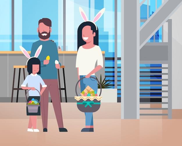 自宅で祝う花を持つ子供を持つ幸せなイースター休暇の両親でかわいい家族