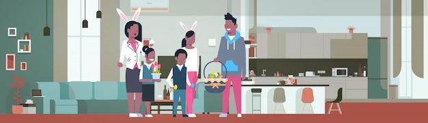 アメリカの家族は幸せなイースター休暇を祝う自宅の居間でバニーの耳を着用