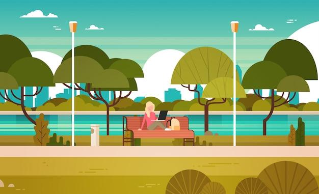 Молодая девушка в парке работает на ноутбуке на открытом воздухе, сидя на скамейке