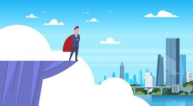 近代的な都市を見て山の端に立っている赤いケープを着ているビジネスマン