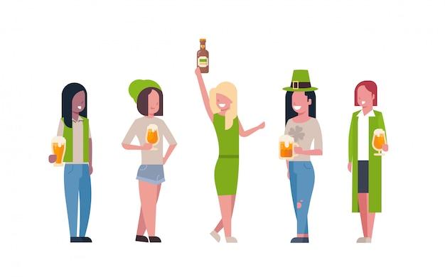Группа женщин смешанной расы в зеленых одеждах пьют пиво, празднуя счастливый день святого патрика