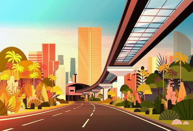 近代的な高層ビルや鉄道の街並みの眺めと夕日の街のスカイラインへの高速道路の道