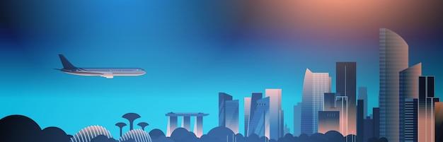 夜にシンガポールのスカイラインを飛ぶ有名なランドマークや高層ビルの美しい街並み