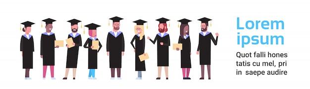 卒業の帽子およびガウンの多様な学生のグループは卒業証書の全長を握ります