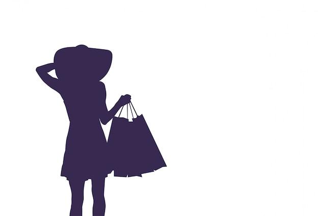 買い物袋を保持しているシルエット女性。販売と割引の概念