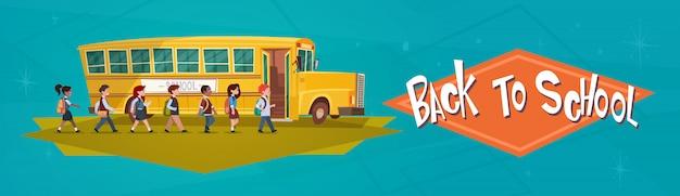 学校に戻って乗って黄色のバスに歩いている生徒グループ