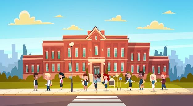 学校の建物小学校の前に生徒ミックスレーススタンドのグループ