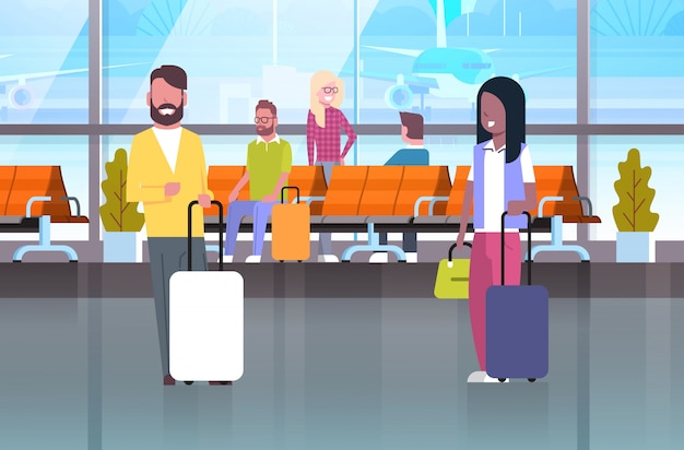 待っているホールでスーツケースを持って旅行者のカップル