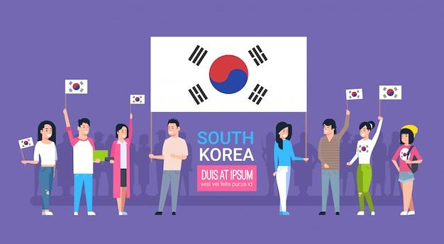 韓国の国旗を保持している若い人々のグループ韓国青年男性と女性