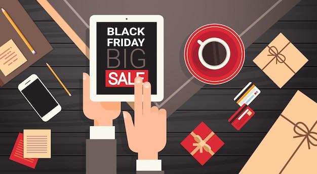 職場のデスクとブラックフライデーのビッグセールメッセージトップビューでデジタルタブレットを持っている手