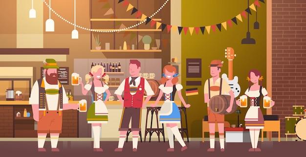人々のグループは、バーでビールを飲みますオクトーバーフェストパーティーのお祝い男と女の伝統的な服祭りのコンセプト