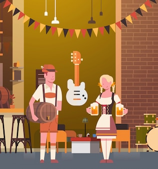 伝統的な服を着てパブのカップルオクトーバーフェストパーティーのお祝いの男と女の祭りのコンセプトでバーでビールを飲む