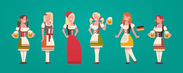 オクトーバーフェストコンセプトのビールジョッキを保持しているドイツの伝統的な服を着ている女性のウェイトレスのグループ