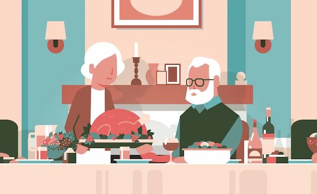 感謝祭を祝うテーブルに座って幸せな感謝祭の老夫婦