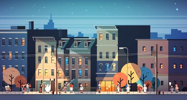 夜の街のバナーを歩くモンスター衣装を着た子供たち