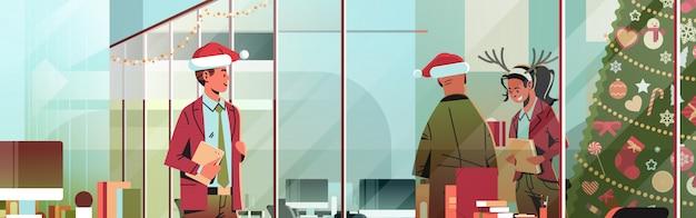 Деловые люди, носящие красную шляпу, работающую в современном офисе