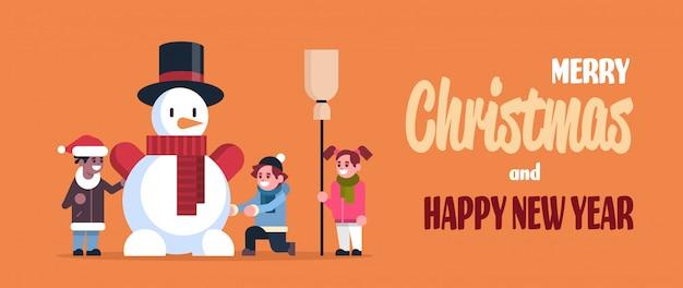 メリークリスマスと幸せな新年のグリーティングカードの雪だるまを作る子供たち