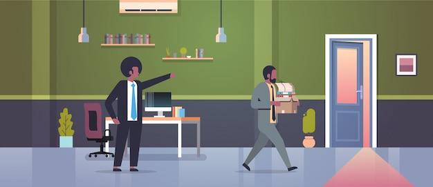 Мужчина босс увольняет указывая пальцем на дверь уволен человек сотрудник с бумажными документами коробка увольнение безработица безработный концепция квартира современный офис