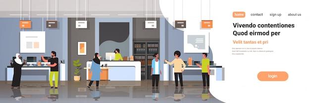 Микс расы покупателей в современном магазине технологий интерьера посетителей, выбирающих цифровой компьютер экран ноутбука смартфона рынок электронных гаджетов