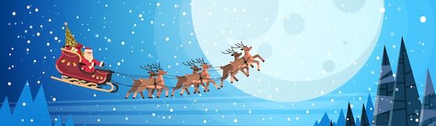 Санта-клаус летит в санях с оленями ночного неба над луной на рождество