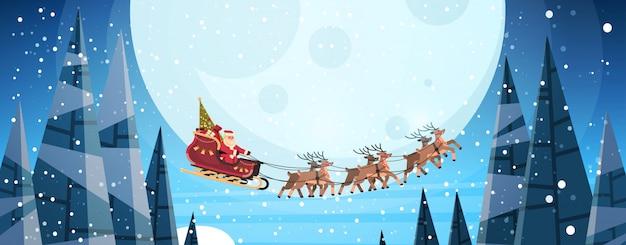 クリスマスの月にトナカイの夜空とそりで飛んでいるサンタクロース