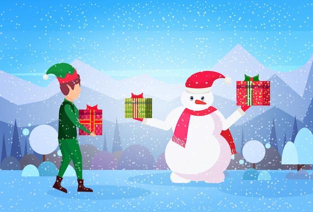 男性エルフと雪だるまは、ラップされたギフトボックスを保持します。