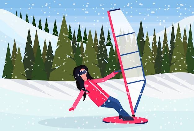 雪の中でウィンドサーフィンをしている女性