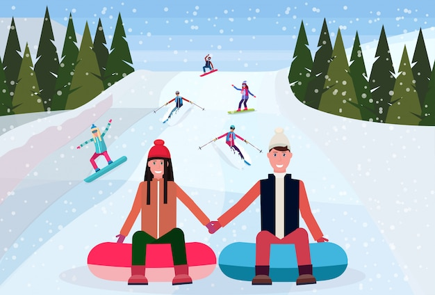 山の雪のゴム管でそりのカップル
