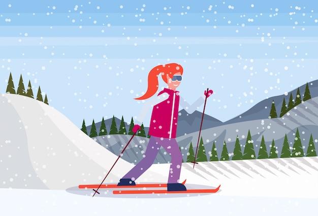 山を滑り落ちるスキーヤーの女性