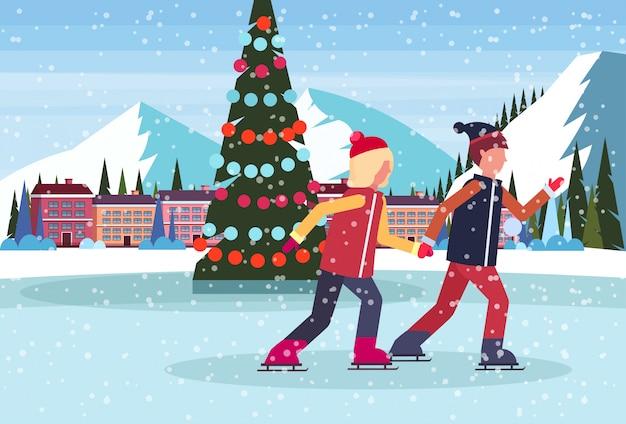 スキーリゾートホテルで飾られたクリスマスツリーとアイススケートリンクでスケートカップル