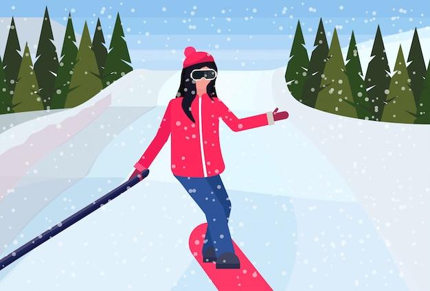 Сноубордист женщина сползает с горы и принимает селфи