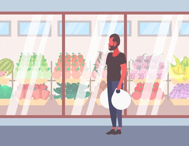 Случайный человек, держащий хозяйственные сумки, идущие перед свежими органическими фруктами овощи современный супермаркет магазин стеклянное окно парень клиент полная длина мультипликационный персонаж квартира