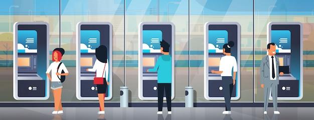 Люди, использующие платежные терминалы самообслуживания банкоматов