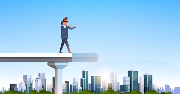 Бизнесмен идет с завязанными глазами на сломанном мосту
