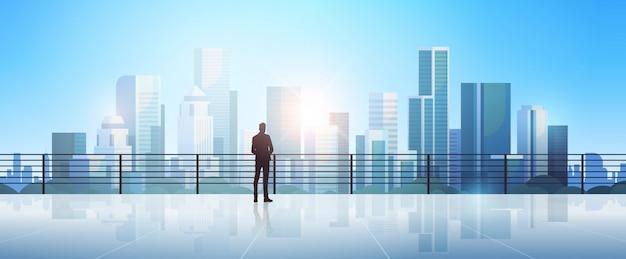 近代的な都市の上に立っている実業家シルエット