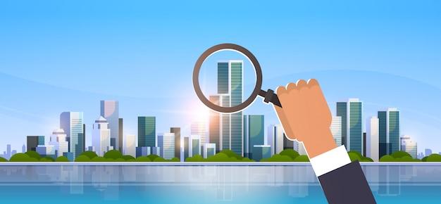大きな近代的な都市の建物の上に虫眼鏡を持っているビジネスマン手