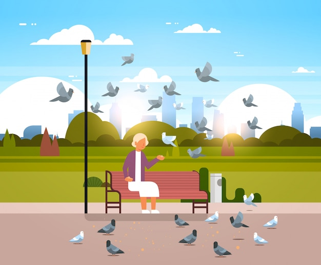 Пожилая женщина кормит стая голубей