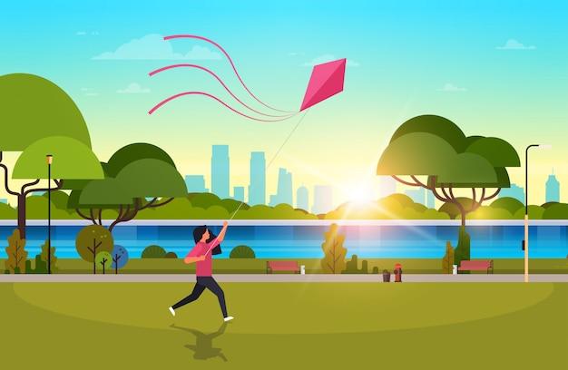 Молодая женщина запускает кайт на открытом воздухе в общественном парке
