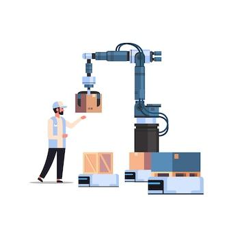 ロボットにボックスを入れてロボットの手を制御する男性エンジニア