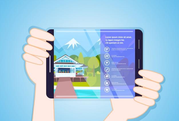 Руки держат планшет с приложением жилья
