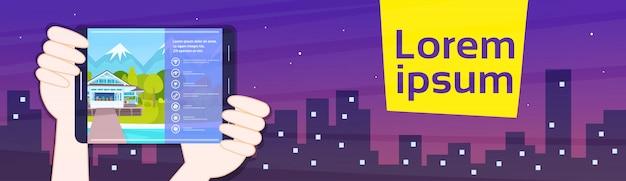 Руки держат планшет с баннером приложение жилья