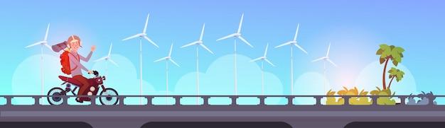 Человек турист езда скутер или мотоцикл с рюкзаком внутри города пейзаж энергия ветра турбины концепция возобновляемых источников чистой энергии