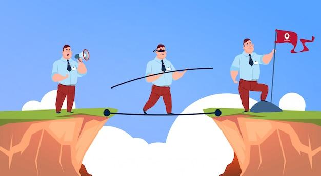 ビジネスマンはメガホンで話す、奈落の底山の上のジオロケーションフラグを持つビジネスの男性に目を閉じてロープに沿って行く