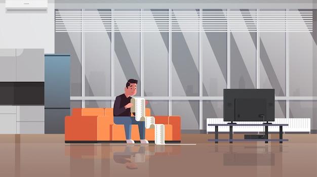 Подчеркнул человек с длинным налоговым документом должник в шоке от оплаты счетов финансовый кризис банкротство концепция парень, сидя на диване беспокоит выплата много денег интерьер гостиной горизонтальный