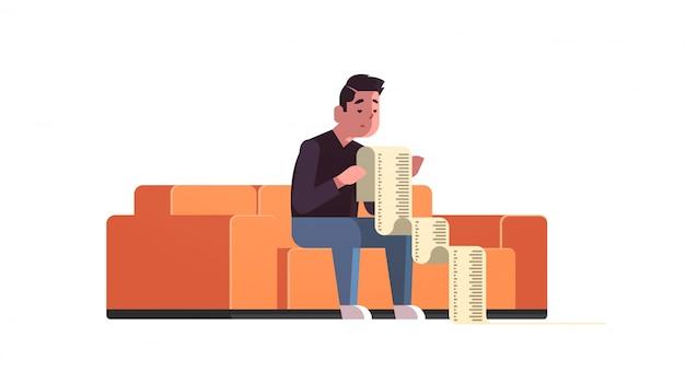 水平方向の多くのお金を払って心配してソファに座って支払手形金融危機破産概念倒産によってショックを受けた長い税務文書の債務者とビジネスマンを強調
