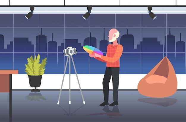 カラーパレットを保持している男性デザイナーのサンプルブロガー三脚にデジタルカメラでオンラインビデオを記録するソーシャルネットワークブログコンセプトモダンなデザインスタジオインテリア全長水平