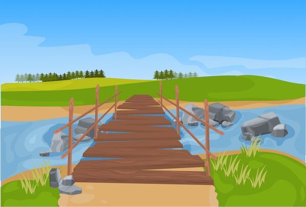 川の山の風景を渡る木製の橋