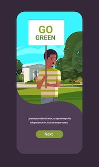 Экологический активист держит плакат идти зеленый сохранить планета забастовка мужчина протестующий кампания по защите земли демонстрации от глобального потепления портрет мобильное приложение вертикальный копией пространства