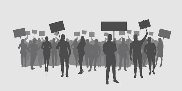 抗議ポスターを保持している抗議者の群衆のシルエット