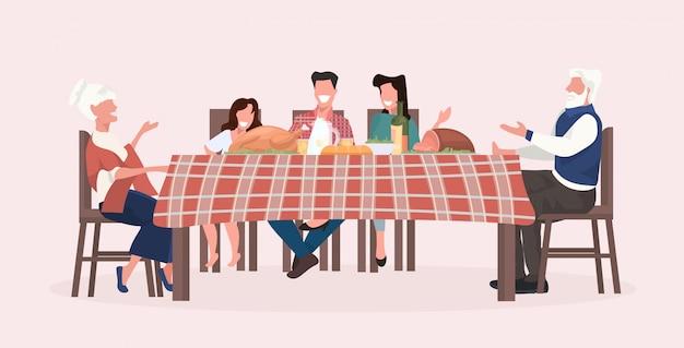 Семья нескольких поколений сидя на столе имея рождественский ужин